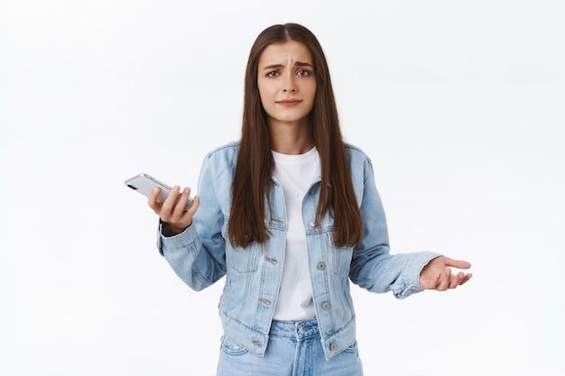 Giovane donna frustrata turbata e dispiaciuta in giacca di jeans, jeans, allarga le mani di lato per lo sgomento, tiene in mano lo smartphone, si acciglia e sorride delusa, in piedi sfondo bianco confuso