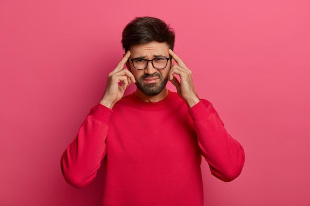 Обеспокоенный, обеспокоенный бородатый мужчина держит указательные пальцы на висках, чтобы сосредоточиться
