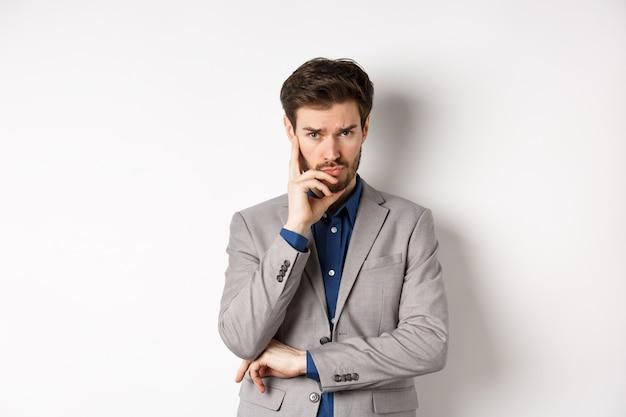カメラを物思いにふける、考えている、または決定を下しているスーツを着て困っている眉をひそめているビジネスマン