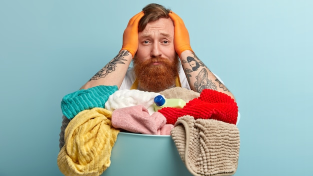 Troubled ginger young man keeps hands on head, looks desperately, wears protective gloves, has tattooed arms, sorrowful facial expression, stands against blue wall. people, domestic work.
