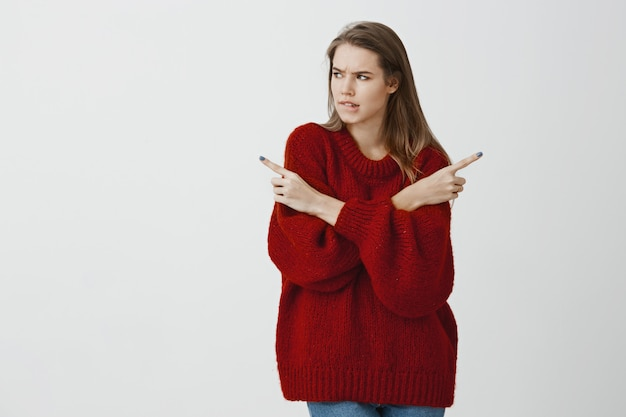 Troubled girl making tough deicison. doubtful attractive woman in loose red sweater, crossing hands and pointing in different directions, biting lip nervously, wanting something over gray wall