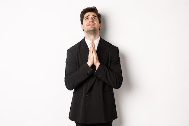 Uomo turbato e pieno di speranza in abito nero che implora dio, supplica e alza lo sguardo, ha bisogno di aiuto, in piedi su sfondo bianco.