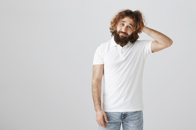 Troubled and indecisive middle-eastern man scratch head clueless