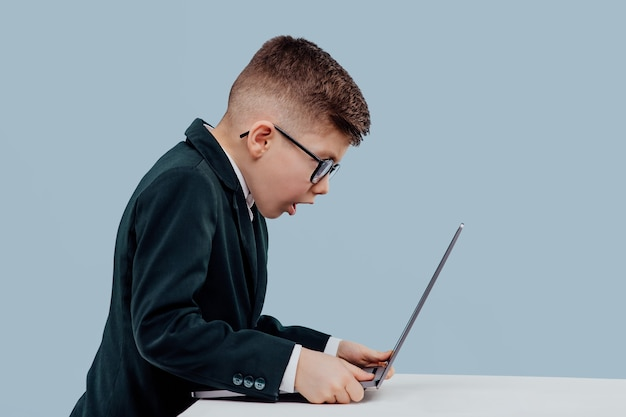 Troubled little boy in suit and glasses and reading data from laptop while working on business proje...
