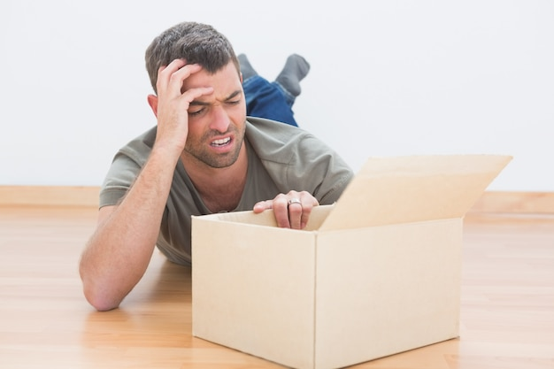 Troubled man open a moving box at home in the living room