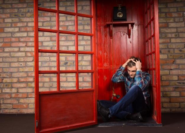 Обеспокоенный мужчина сидит на полу в углу телефонной будки и держит голову руками