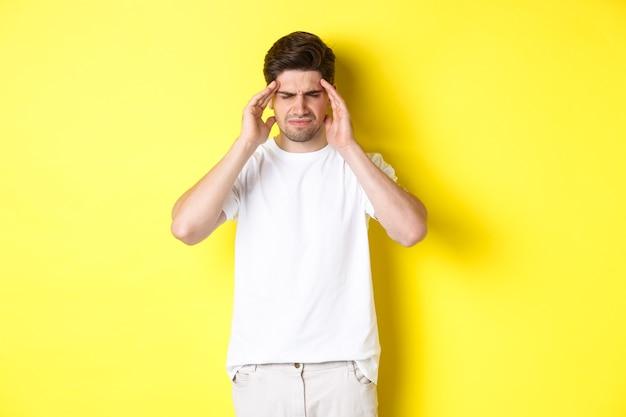 頭に触れて痛みから顔をゆがめ、頭痛を訴え、黄色の背景の上に立っている問題を抱えた男。コピースペース