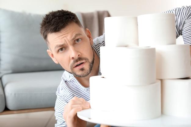 Беспокойный человек с кучей туалетной бумаги дома. концепция эпидемии коронавируса