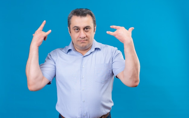 Troubled middle-aged man in blue striped shirt holding hands in the rock symbol on a blue background