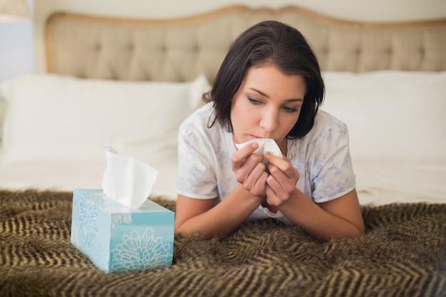 Тревожная довольно коричневая волосатая женщина плачет на своей кровати