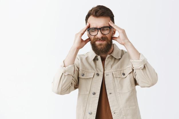 Обеспокоенный больной бородатый мужчина в очках позирует на фоне белой стены