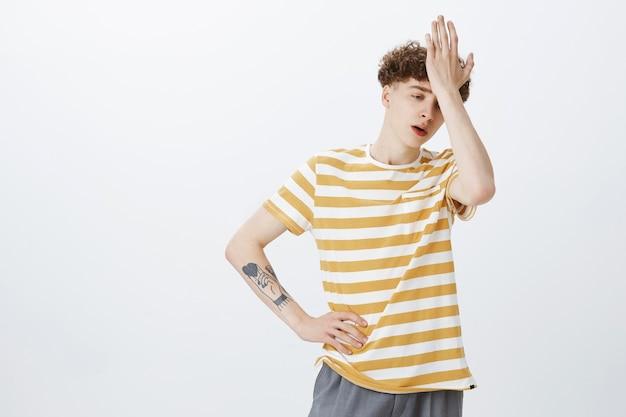 Ragazzo adolescente turbato in posa contro il muro bianco