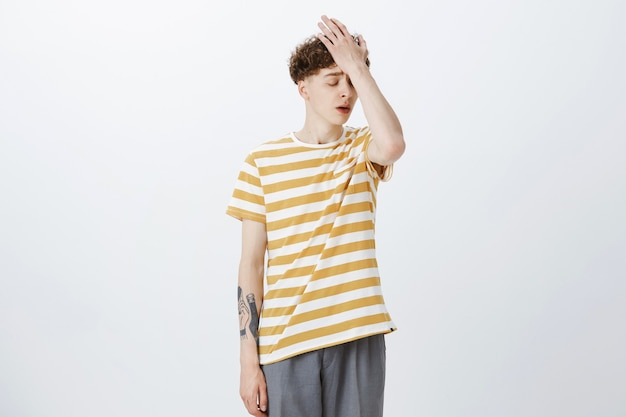 Troubled teenage guy posing against the white wall