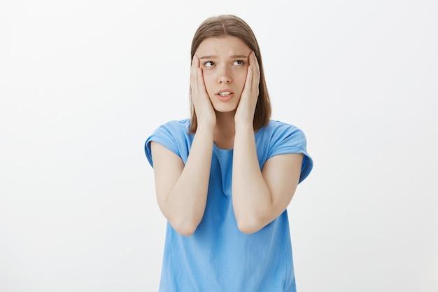 У обеспокоенной женщины большая проблема, она держится за голову и в отчаянии смотрит в правый верхний угол
