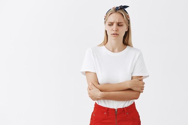 Обеспокоенная молодая блондинка позирует у белой стены