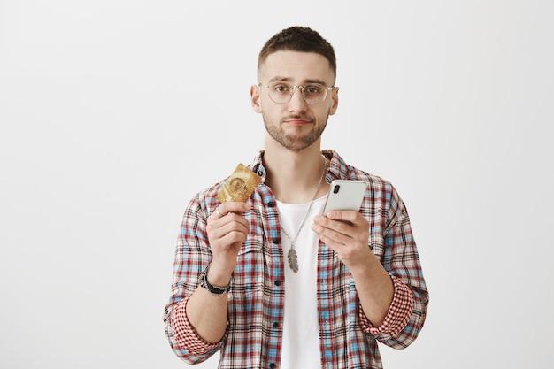 彼の電話とカードでポーズをとって眼鏡をかけた問題を抱えた若い男