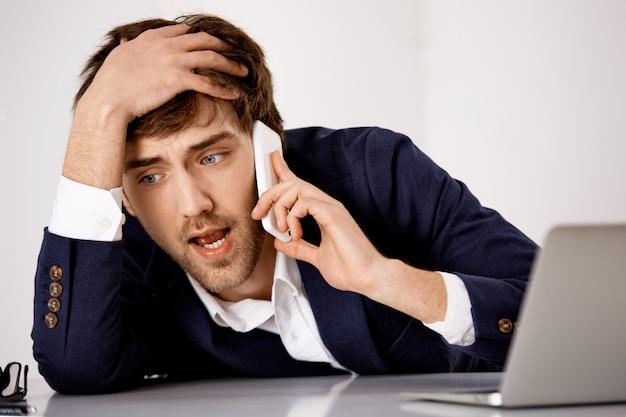問題を抱えた若い男、苦しめられたテーブルに寄りかかる、電話で深刻な会話をしている、ビジネスパートナーとの大きな問題
