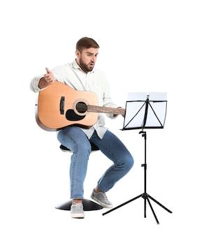 Обеспокоенный молодой человек играет на гитаре на белой поверхности