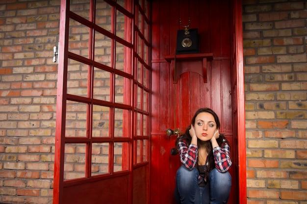 開いたドアの赤い電話ブースでしゃがみ耳を渡して問題を抱えた若い女性