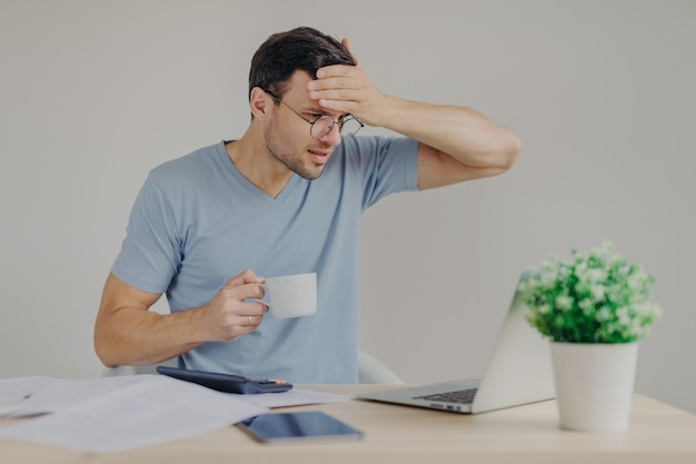 Troublesome brunet man in casual t shirt, has headache as calculates his expenses