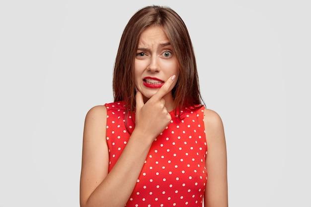 Проблемная озадаченная кавказская женщина хмурится, стискивает зубы, поднимает брови, держится за подбородок, у нее проблемы