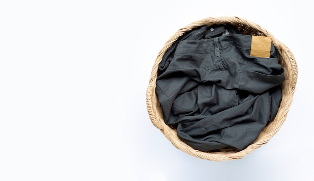 Trousers in laundry basket on white surface. copy space