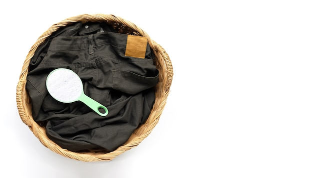 Trousers with measuring spoon of detergent powder in laundry basket on white background. copy space