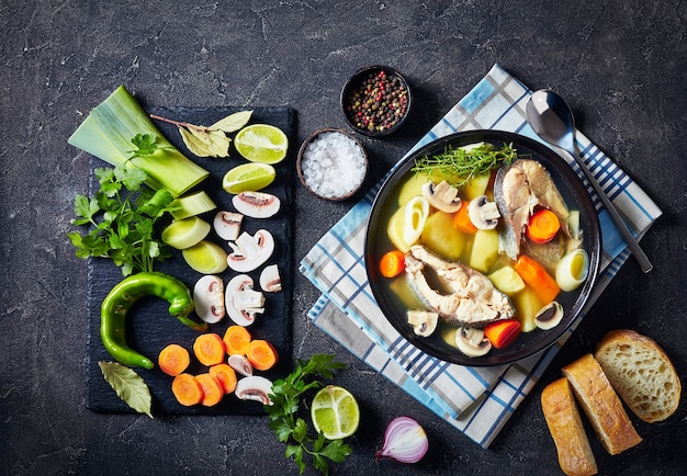 Trout fish soup with vegetables and mushrooms served in a black bowl on a concrete table with ingredients on a slate board, silver spoon on a napkin, horizontal view from above, free space, flatlay