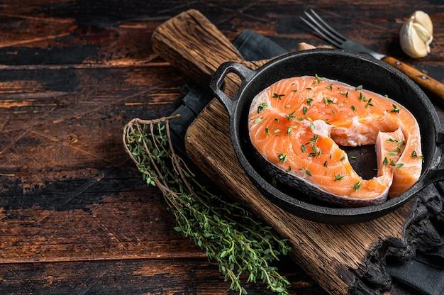 Сырые стейки форели или лосося на сковороде с тимьяном. темный деревянный фон. вид сверху. скопируйте пространство.