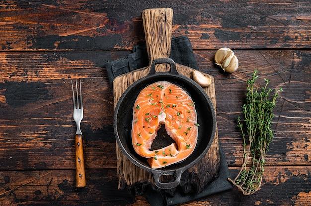 Сырые стейки форели или лосося на сковороде с тимьяном. темный деревянный фон. вид сверху.