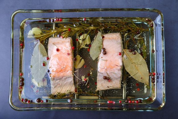 Trout (salmon) in oil with herbs and spices, cooked by the confit method. traditional french dish. step by step. close-up.