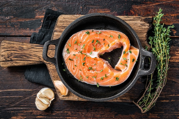 Trout or salmon raw steaks in a pan with thyme. dark wooden background. top view.