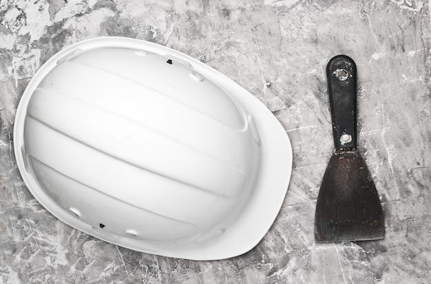 Мастерок и строительный шлем на сером бетонном фоне. строительное оборудование. вид сверху