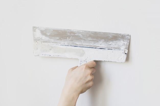 白い壁の男の手にこて。修理用の汚れた工具。