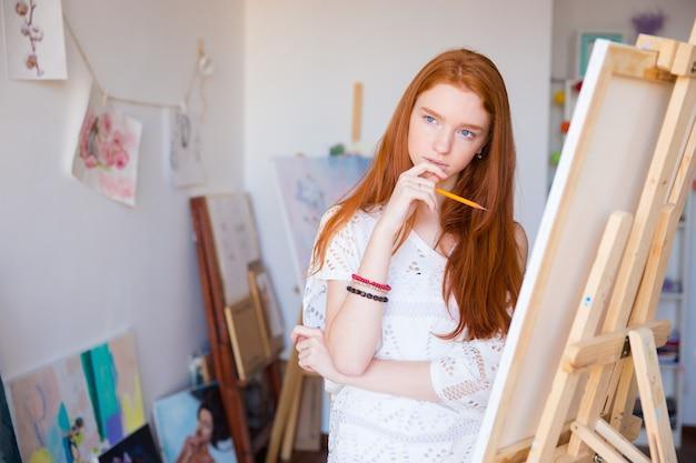 Трактивная задумчивая художница с красивыми длинными рыжими волосами думает и делает