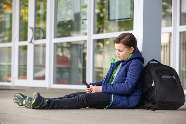 Truancy concept, young boy staying away from the school and playing games on the mobile, absence from school