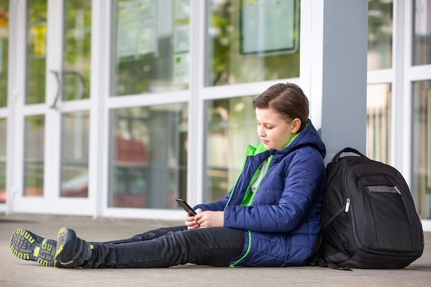 Truancy concept, young boy staying away from the school and playing games on the mobile or smartphone, absence from school