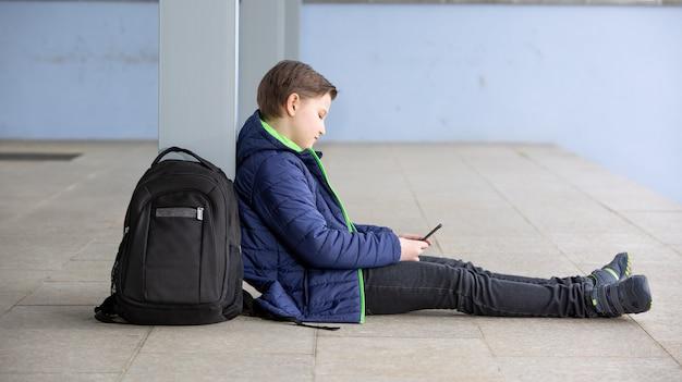 Концепция прогулов, мальчик не посещает школу и играет в игры на мобильном телефоне или смартфоне, отсутствие в школе