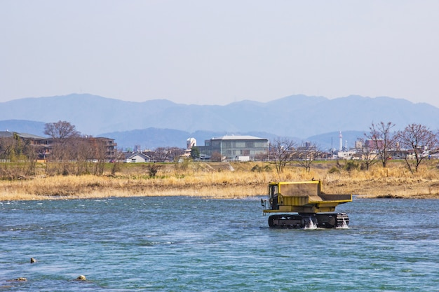 Truck and dredging stone in river katsura for to make water flow