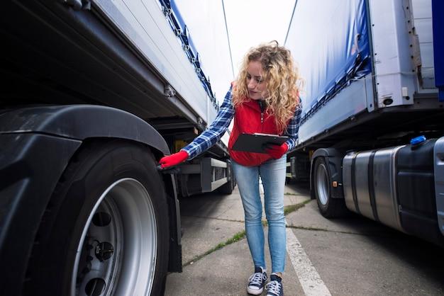 Водитель грузовика проверяет шины транспортного средства и осматривает грузовик перед поездкой