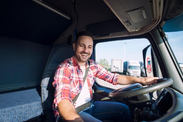 Autista di camion che guida il suo camion e cambia stazione radio per riprodurre la sua musica preferita