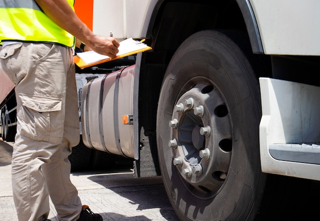 Truck driver hand holding clipboard with inspecting a truck tires.