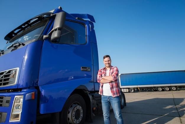 팔을 가진 그의 트럭 옆에 서있는 캐주얼 옷을 입은 트럭 운전사가 트럭 정류장에서 넘어