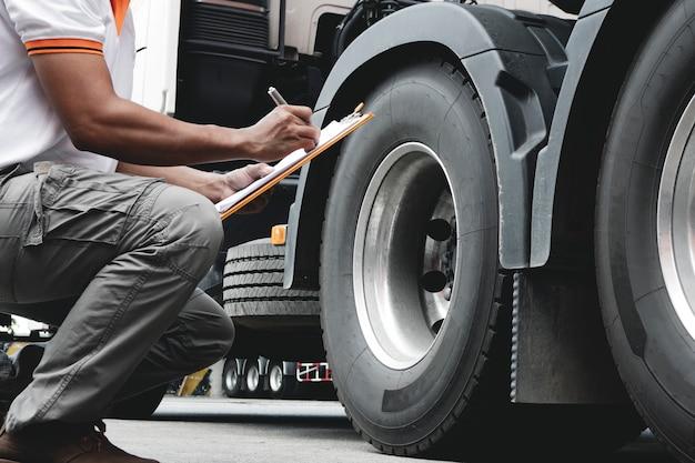 Водитель грузовика осматривает детали контрольного перечня безопасности грузовых шин.