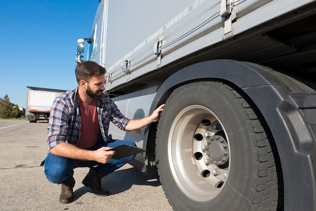 Truck driver inspecting tires and checking depth of tire tread for safe ride