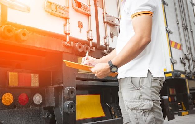 트럭 운전사가 트럭 안전 유지 관리 체크리스트를 확인하고 있습니다.
