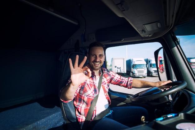 그의 직업을 사랑하고 그의 트럭 오두막에 앉아있는 동안 괜찮은 제스처 기호를 보여주는 트럭 운전사