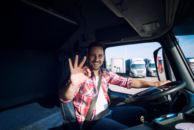 Truck driver loving his job and showing okay gesture sign while sitting in his truck cabin