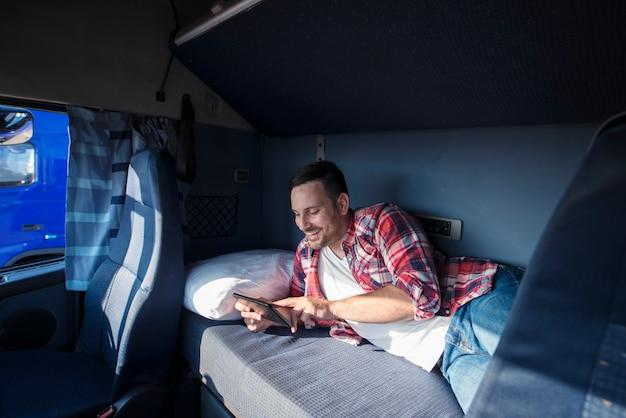 Autista di camion sdraiato sul letto nella sua cabina che comunica con la sua famiglia tramite computer tablet