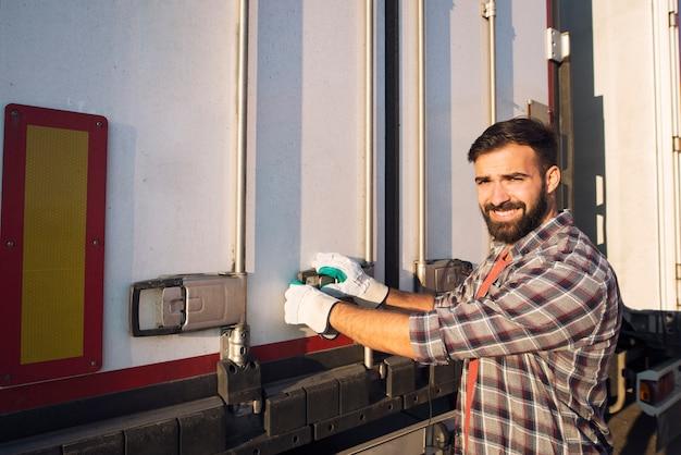 화물을 내리기 위해 트럭 트레일러 뒤쪽을 여는 트럭 운전사